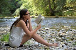 ung pige der læser ved flodbredden