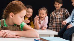 Børn griner af en pige som sidder i forgrunden af billedet.