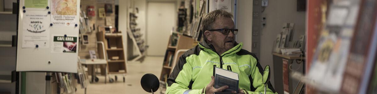 Låner med bog i hånden på Fuglebjerg Bibliotek