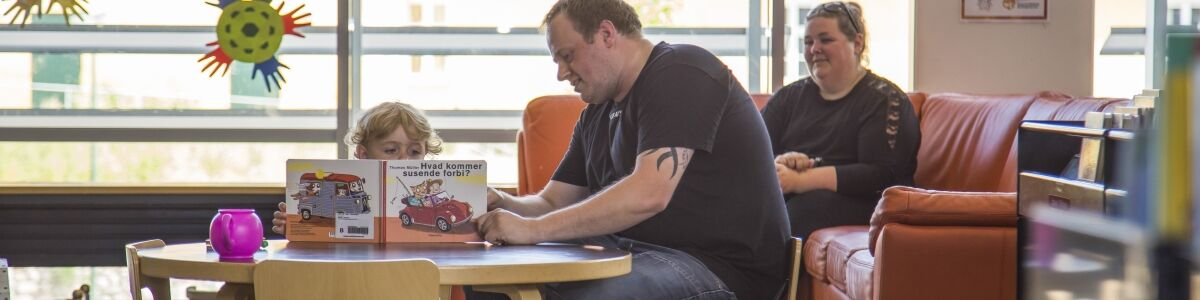 Foto af far, der læser med barn på Næstved Bibliotek