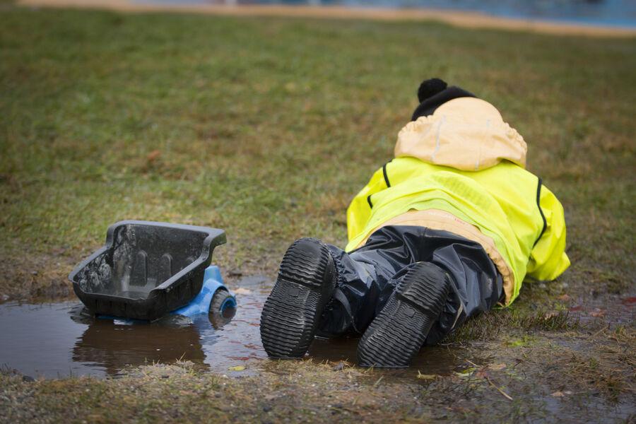 Et barn, der ligger ned i mudder i regnvejr