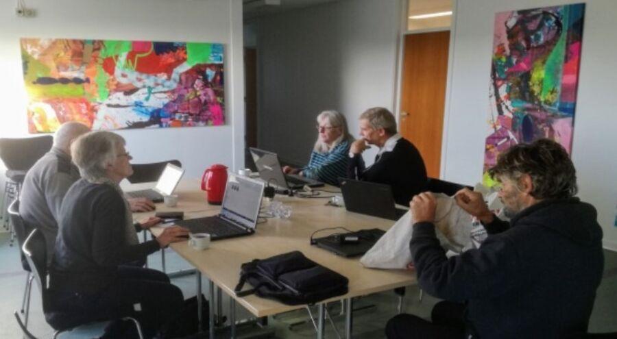 Mennesker der sidder ved et rundt bord og arbejder ved computere