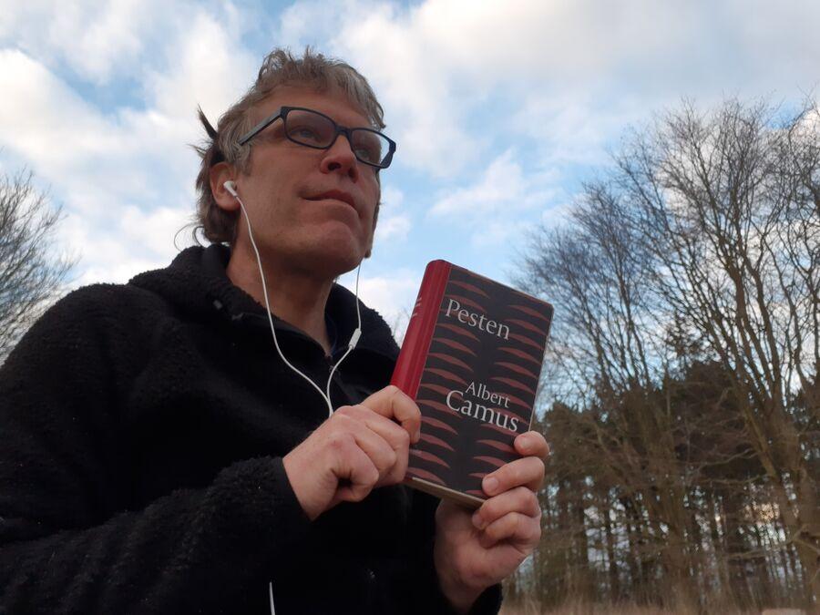 Thomas holder romanen Pesten i hænderne, mens han kigger ud i luften