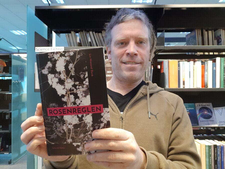 Thomas står med romanen Rosenreglen i hænderne