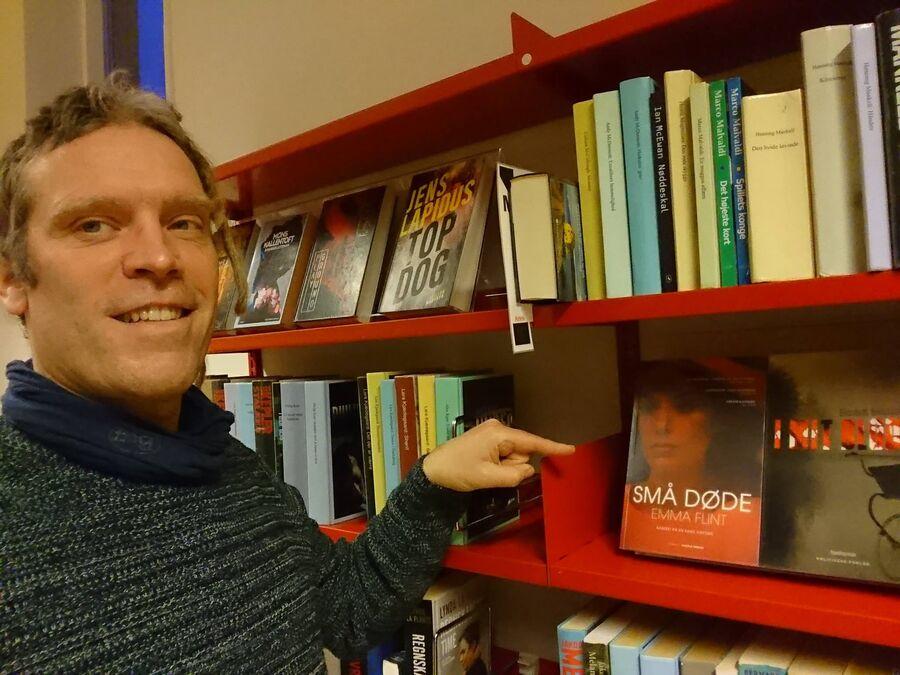 Foto af Thomas Damholt, der peger på bogen: Små døde på Glumsø Bibliotek
