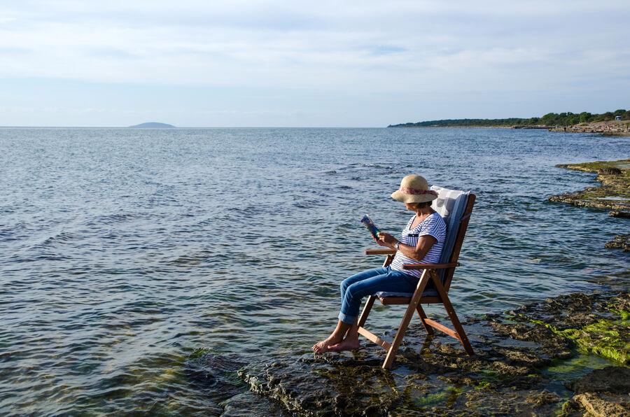 Dame, der sidder i vandkant og læser i en bog