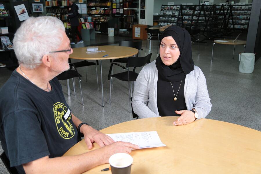 Foto af to, der snakker sammen ved bord på Næstved Bibliotek