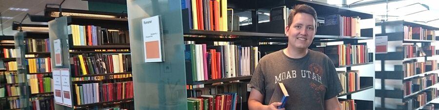 Foto af Jesper Christensen, der holder en bog