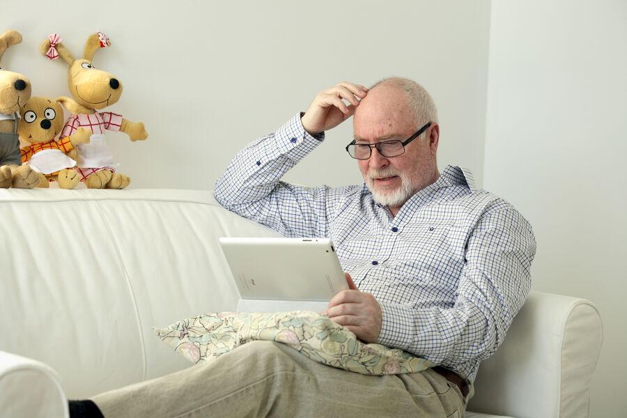 Foto af ældre herre, der læser på en tablet i en sofa