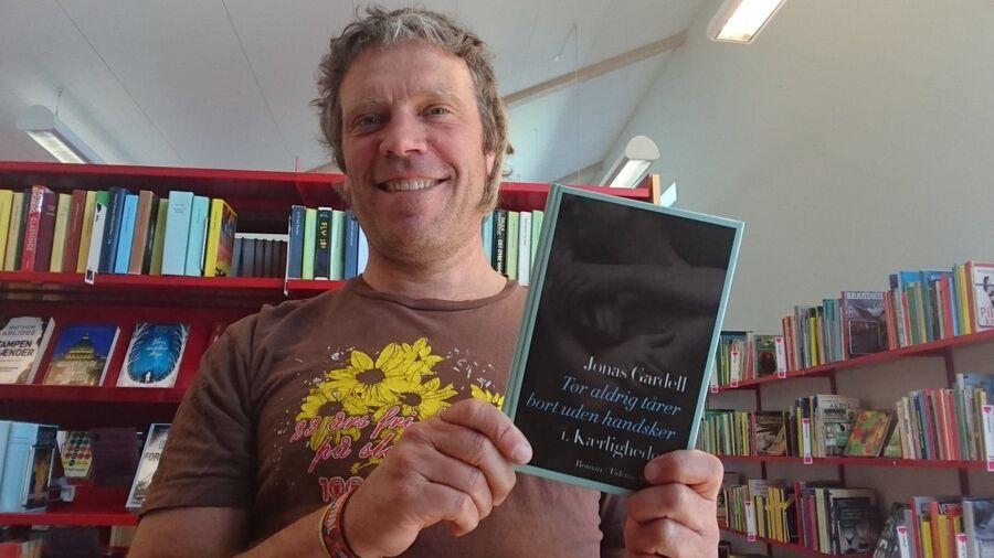 Bibliotekar Thomas står med bogen Tør aldrig tårer bort uden handsker, bind 1: Kærligheden