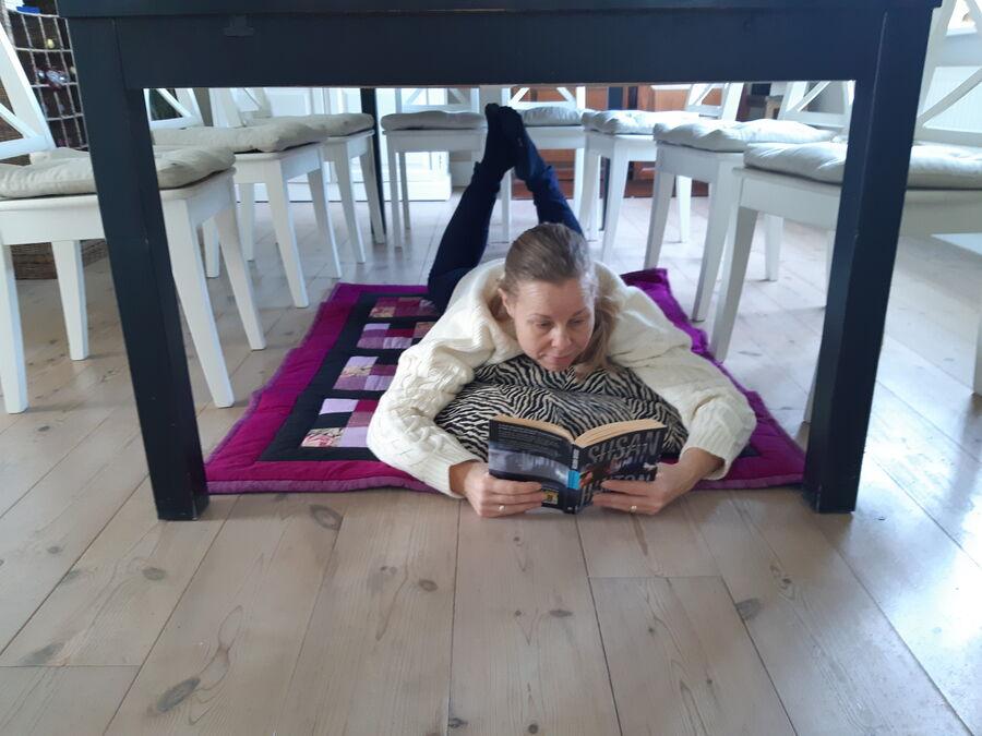 Eva læser under spisebord